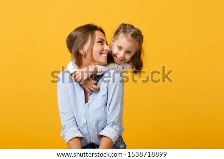 Woman in light clothes have fun with cute child baby girl 4-5 years old. Mommy little kid daughter isolated on yellow background studio portrait. Mother's Day love family parenthood childhood concept Royalty-Free Stock Photo #1538718899