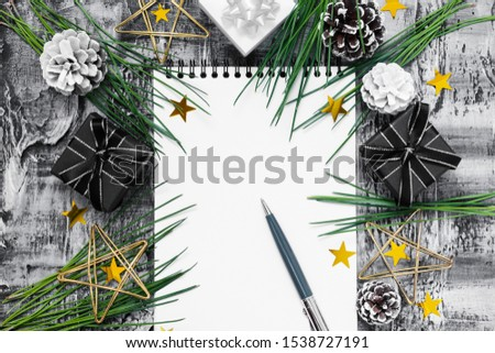 Holiday Christmas frame decor on black stucco concrete backdrop. Fir branch, gold stars, confetti, white, black gift boxes, cones, notepad, pe. Elegant New Year`s flat lay, christmas decor. Copy space #1538727191