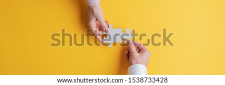 Wide view image of male and female hand joining two matching puzzle pieces together in a conceptual image of teamwork and cooperation. Top view with copy space. #1538733428