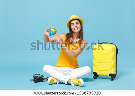 Traveler tourist woman in yellow casual clothes hat with suitcase photo camera isolated on blue background. Female passenger traveling abroad to travel on weekends getaway. Air flight journey concept #1538733920
