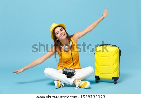 Traveler tourist woman in yellow casual clothes hat with suitcase photo camera isolated on blue background. Female passenger traveling abroad to travel on weekends getaway. Air flight journey concept #1538733923