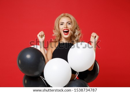 Ovejoyed young woman girl in black clothes posing isolated on red background. New Year 2020 birthday holiday party concept. Mock up copy space. Celebrating holding air balloons doing winner gesture #1538734787