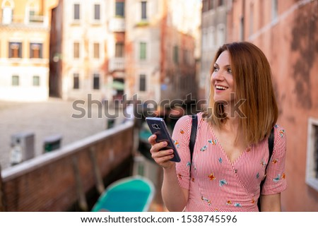 Italian holiday. Woman is found the direction on her phone, walking through the canals in Venice. European popular tourist destination.  #1538745596