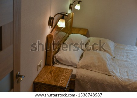 Bed in a hotel room. Bed and pillows. A bed with a wooden headboard and two cabinets and floor lamps. Day or evening hotel. Place for sleeping and relaxing. Rectangular pillows in a white pillowcase #1538748587