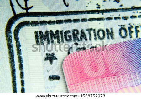 "UK BRP Tier 2 visa card on top of immigration stamp in passport where the only letters ""IMMIGRATION OFF"" visible from whole phrase  ""IMMIGRATION OFFICER"". Strong concept for UK - EU relationship. Royalty-Free Stock Photo #1538752973"