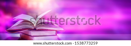 Imagine a picture book of an ancient book opened on a wooden table with a sparkling golden background. With magical power, magic, lightning around a glowing glowing book In the room of darkness #1538773259
