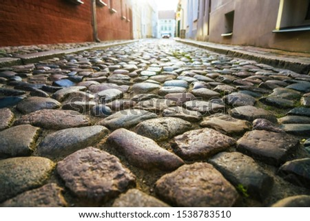 Old town in Europe at sunset with retro vintage cobble stone. cobble paving Stone background for walking. Cobblestone street in sunlight with a wall made from granite blocks #1538783510