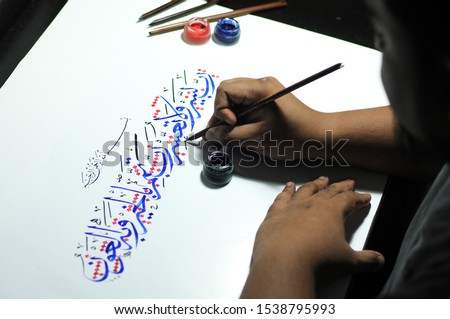 """Oh Allah, make this task easy and do not make it difficult. Oh Allah! Make it end well"" - Translation Arabic CalligraphyA Man Writing Arabic Calligraphy on White Paper using red and blue ink."
