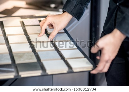 Male architect or interior designer hand choosing ceramic texture sample from swatch board in design studio. Floor and wall finishing material for architecture and construction industry. Royalty-Free Stock Photo #1538812904