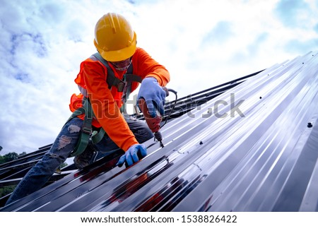 Roofer working on roof structure of building on construction site,Roofer using air or pneumatic nail gun and installing Metal Sheet on top new roof. #1538826422
