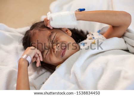 Sick asian child girl who have IV solution bandaged suffering from headache and feeling unwell in the hospital #1538834450