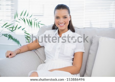 Cheerful woman in white dress sitting on sofa in bright living room #153886496
