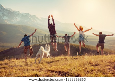 Group of happy friends are having fun, runs and jumps in mountains at sunset #1538866853