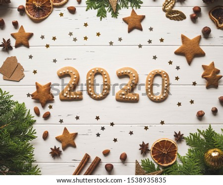 Gingerbread of the form of numbers  2020 new year ginger cookies, confetti f gold stars, spices and firs on white wood background. Top view.  #1538935835