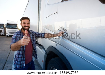 Truck driver occupation. Professional middle aged bearded trucker standing by his semi truck and holding thumbs up. Successful and fast transportation service. #1538937032