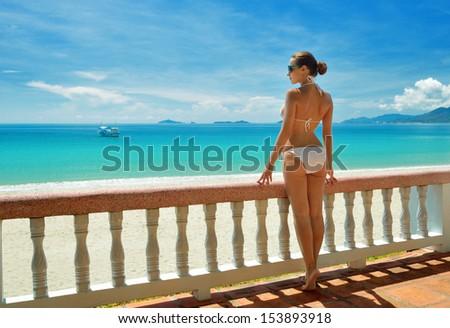 Beautiful woman in bikini on the terrace admiring the sea. #153893918