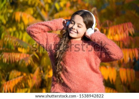 feeling inspired with favorite song. little child in headset. enjoy autumn day. good day for park walk. she love nature and music. feel real joy. fall mood melody. small girl listen audio book. #1538942822