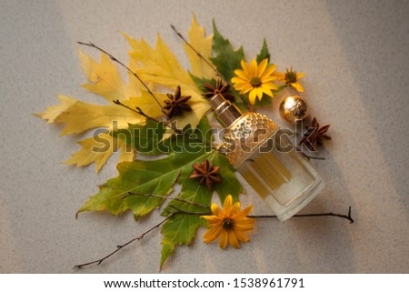 glass perfume bottle with a gold insert with autumn leaves. twigs, yellow flowers and anise stars #1538961791