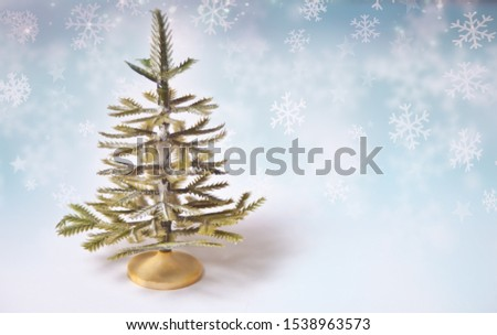 Miniature evergreen Christmas tree on a snowflake blue background #1538963573