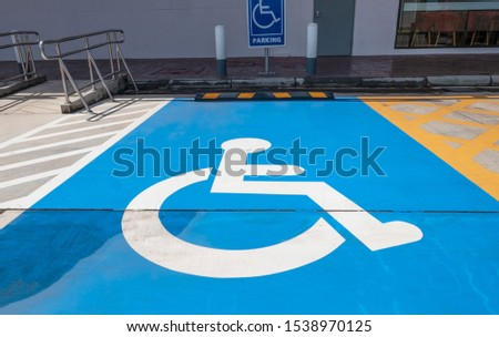 traffic sign about handicapped symbol painted in bright blue . Disabled parking spaces .