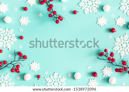 Christmas or winter composition. Snowflakes and red berries on mint background. Christmas, winter, new year concept. Flat lay, top view, copy space #1538972096