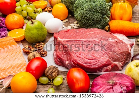 Trending paleo/pegan diet. Healthy balanced food concept. Set of fresh products, raw meat, salmon, vegetables and fruits. Old wooden boards background #1538972426