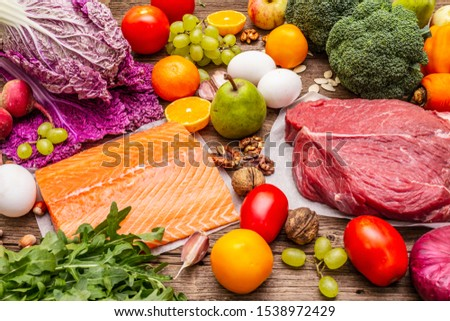 Trending paleo/pegan diet. Healthy balanced food concept. Set of fresh products, raw meat, salmon, vegetables and fruits. Old wooden boards background #1538972429