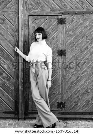 High waisted trousers. Woman attractive brunette wear fashionable clothes. Femininity and emphasize feminine figure. Girl wear loose high waisted pants. Fashion shop. High waisted pants fashion trend. #1539016514