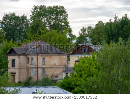 Old shabby houses, surrounded by green trees under a cloudy overcast sky. #1539017552