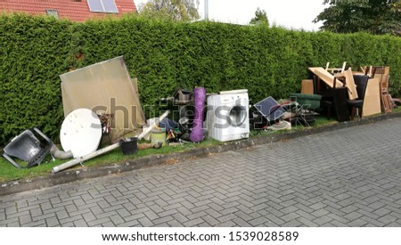 Bulky waste on the street is waiting for garbage collection. Waste collection. Bulky trash, a pile of mixed garbage. Rubbish. Recycling industry. Ecology. Recycled materials and wastes Royalty-Free Stock Photo #1539028589