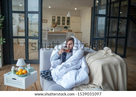 Man feeling cold. Man feeling cold so drinking hot tea and covering in bedsheet in living room #1539031097
