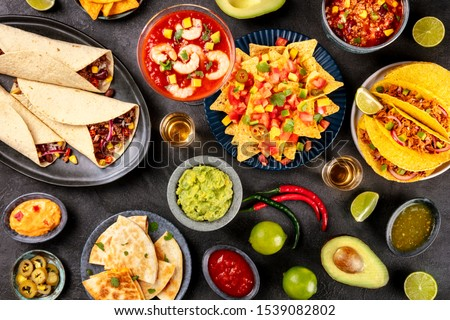 Mexican food, many dishes of the cuisine of Mexico, flat lay, shot from above on a black background. Nachos, tequila, guacamole etc #1539082802