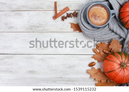 Grey mug of coffee wrapped in plaid or scarf, spices, dry oak leaves, acorns, orange pumpkins on white wooden table. Autumn drink concept. Fall, pumpkin spicy latte, thanksgiving, top, copy space Royalty-Free Stock Photo #1539115232