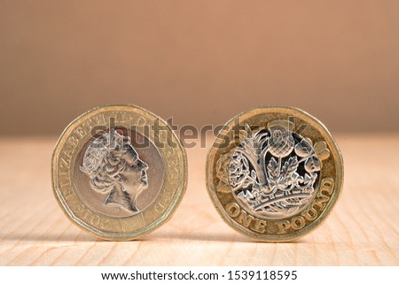 Closeup of  One Pound sterling coin standing on wooden table background. #1539118595