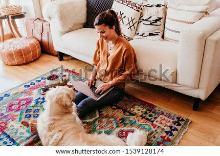young woman working on laptop at home. cute golden retriever dog besides. healthy breakfast time. technology and lifestyle indoors #1539128174
