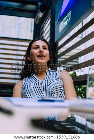 Portrait of pretty young caucasian female doing paperwork in modern office #1539131606