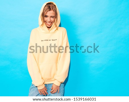 Portrait of young beautiful smiling girl in trendy summer hipster yellow hoodie.Sexy carefree woman posing near blue wall. Positive model having fun.Winks and shows tongue