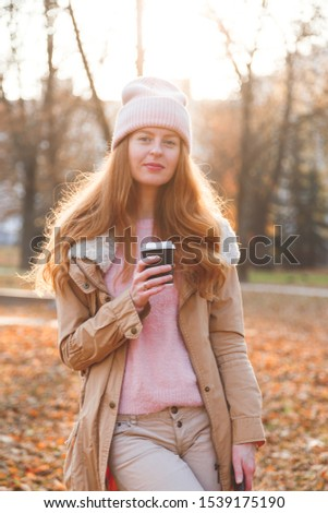 Redhead woman with paper cup in autumn's park #1539175190