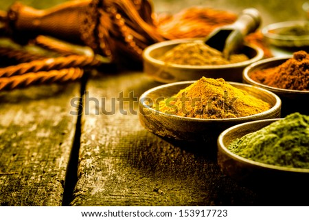 Asian cuisine with a low angle view of bowls of colourful spices with focus to a bowl of turmeric based curry powder #153917723