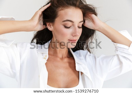 Portrait of an attractive smiling young brunette woman wearing white shirt standing isolated over white background, posing #1539276710