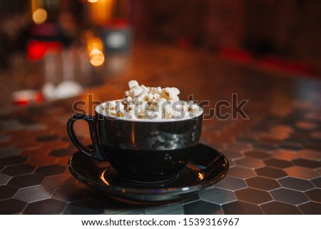 Mug of cappuccino coffee with popcorn on a bar counter in the light of colored lamps. The cup is black. Mosaic table. Cocoa. Great background for Photoshop, suitable in the menu.