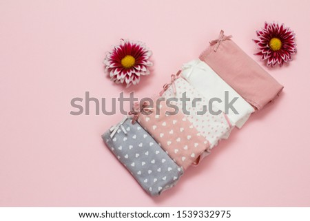 Folded cotton panties of different color with flower buds on pink background. Woman underwear set. Top view.