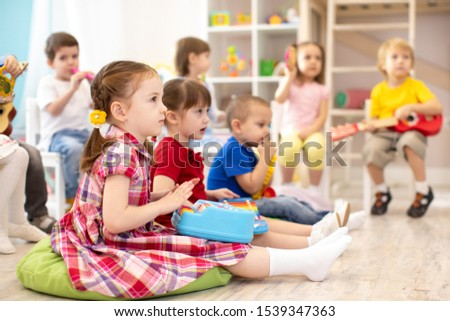 Group of kids 3-4 years old with toy musical instruments. Early music education in kindergarten #1539347363