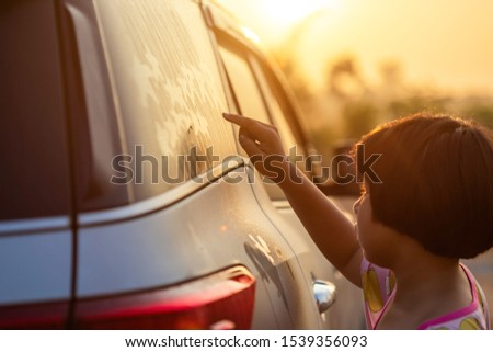 Asian little girl writing or drawing star symbol on wet mirror of her father SUV car in morning for love concept #1539356093