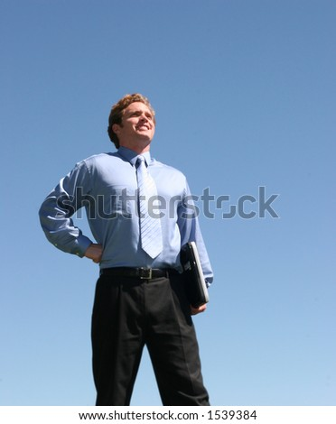 Business man in blue shirt and blue tie, holding laptop against blue sky #1539384