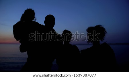 Family silhouette standing against night sea background, unity in difficulties