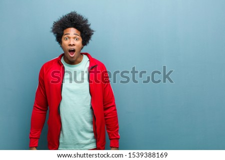 young black sports man looking shocked, angry, annoyed or disappointed, open mouthed and furious against grunge wall #1539388169
