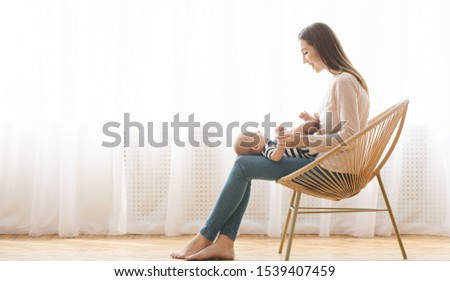Young mother sitting in wicker chair with her newborn baby on lap, side view with free space, panorama #1539407459