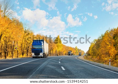 Arriving blue truck on the road in a rural landscape at sunset autumn #1539414251
