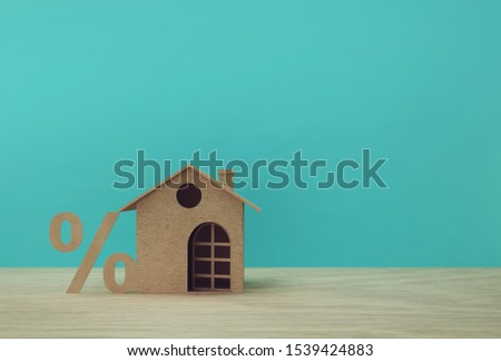 Creative idea of house model paper and percentage sign symbol icon  on wooden table. Property investment real estate and house mortgage financial concept. #1539424883